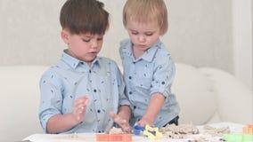 Twee kleine jonge geitjes die met deeg spelen en leren hoe te bakken stock footage