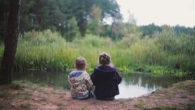 Twee kleine jonge geitjes, een meisje en een jongenszitting op een rivierbank Een meisje eet watermeloen, terug eruit zien zij ba stock videobeelden