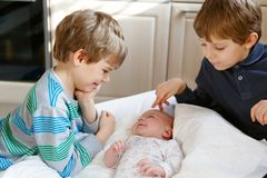 Twee kleine jonge geitjesjongens die met het pasgeboren meisje van de babyzuster spelen stock afbeeldingen