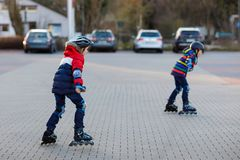Twee kleine jonge geitjesjongens die met rollen in de stad schaatsen Gelukkige kinderen, siblings en beste vrienden in beschermin stock afbeeldingen