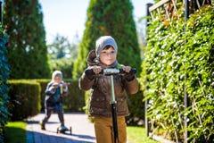 Twee kleine jonge geitjesjongens die op duwautopedden berijden Waarschuw de zomer of de lentedag De jongen die van het broersjong stock fotografie