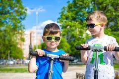 Twee kleine jonge geitjesjongens die op duwautopedden berijden royalty-vrije stock foto