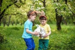 Twee kleine jonge geitjesjongens en vrienden in Paashaasoren tijdens traditioneel ei jagen in de lentetuin, in openlucht Siblings Stock Fotografie