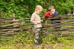 Twee kleine jongens die een bespreking over een omheining hebben Royalty-vrije Stock Foto's