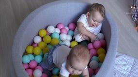 Twee kleine jongens die in een pool van gekleurde ballen spelen De baby krijgt aan zijn voeten stock footage