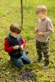 Twee kleine jongens die een smeulende brand doven royalty-vrije stock afbeeldingen