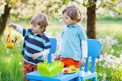 Twee kleine jongens die en kleurrijk ei spelen schilderen Stock Afbeeldingen