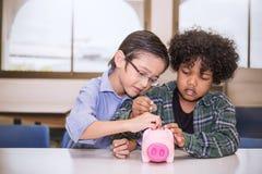 Twee kleine jongens die geld zetten in spaarvarken voor toekomstige besparingen stock foto