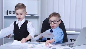 Twee kleine jongens die grafiek en verspreiding op de lijst kijken Langzame Motie stock video