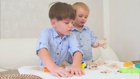Twee kleine jongens die met deeg spelen en leren hoe te bakken stock video