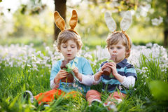 Twee kleine jongens die Paashaasoren dragen en chocolade eten Stock Afbeelding