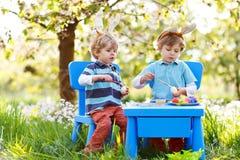 Twee kleine jongens die Paashaasoren dragen, schilderend kleurrijk ei Stock Afbeelding