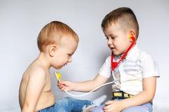 Twee kleine jongens die stethoscoop met behulp van Kinderen die arts en patiënt spelen Controleer de hartslag stock fotografie