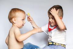 Twee kleine jongens die stethoscoop met behulp van Kinderen die arts en patiënt spelen Controleer de hartslag stock foto