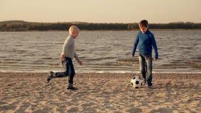 Twee kleine jongens die voetbal op het strand spelen stock video