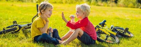 Twee kleine jongens drinken water in het park na het berijden van een fietsbanner, LANG FORMAAT stock foto