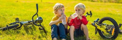 Twee kleine jongens drinken water in het park na het berijden van een fietsbanner, LANG FORMAAT royalty-vrije stock afbeelding