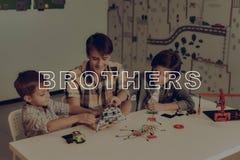 Twee Kleine Jongens en Jong Guy Robots Constructing stock foto's