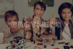 Twee Kleine Jongens en Jong Guy Robots Constructing royalty-vrije stock fotografie