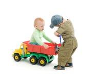 Twee kleine jongens spelen met stuk speelgoed vrachtwagen Royalty-vrije Stock Foto's