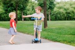 Twee kleine Kaukasische peuterkinderen die in park buiten vechten De jongen en het meisje kunnen niet ??n autoped delen stock foto's