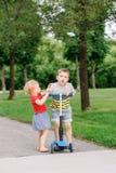Twee kleine Kaukasische peuterkinderen die in park buiten vechten De jongen en het meisje kunnen niet ??n autoped delen royalty-vrije stock afbeelding