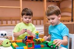 Twee kleine Kaukasische vrienden die met veel kleurrijke plastic blokken spelen binnen Actieve jong geitjejongens, siblings die p Stock Foto