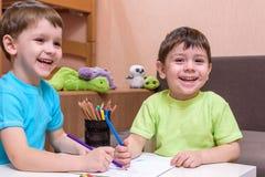 Twee kleine Kaukasische vrienden die met veel kleurrijke plastic blokken spelen binnen Actieve jong geitjejongens, siblings die p Royalty-vrije Stock Foto