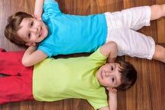 Twee kleine Kaukasische vrienden die met veel kleurrijke plastic blokken spelen binnen Actieve jong geitjejongens, siblings die p Royalty-vrije Stock Afbeelding
