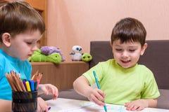 Twee kleine Kaukasische vrienden die met veel kleurrijke plastic blokken spelen binnen Actieve jong geitjejongens, siblings die p Stock Foto's