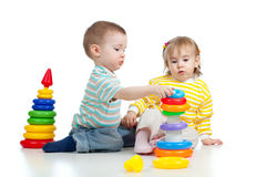 Twee kleine kinderen die met kleurenspeelgoed spelen Stock Afbeelding