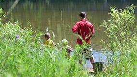 Twee kleine kinderen en een jonge vader die op de rivierbank vissen Mooi de zomerlandschap Openlucht recreatie stock video