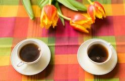 Twee kleine koppen van koffie op de schotels op de lijst met tulpen Royalty-vrije Stock Foto's