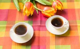 Twee kleine koppen van koffie op de schotels op de lijst met tulpen Stock Foto