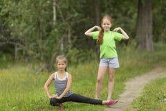 Twee kleine leuke meisjes die in openlucht opwarmen royalty-vrije stock foto's