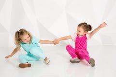 Twee kleine meisjes in de identieke overall van verschillende kleuren die op de vloer in een studio met witte muren zitten Stock Afbeeldingen