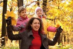 Twee kleine meisjes met moeder in herfstpark Stock Afbeelding