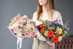 Twee Kleine Mooie boeketten van gemengde bloemen in vrouwenhand Bloemenwinkelconcept Mooi vers besnoeiingsboeket Bloemen royalty-vrije stock foto's