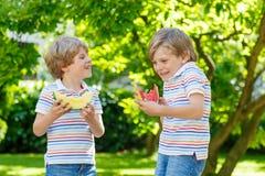 Twee kleine peuterjong geitjejongens die watermeloen in de zomer eten royalty-vrije stock afbeeldingen