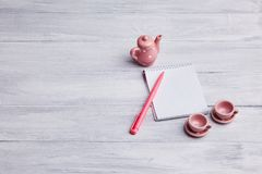 Twee kleine roze theekoppen met ketel op een houten achtergrond Kaart met een notitieboekje en een pen royalty-vrije stock afbeeldingen