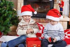 Twee kleine sibling jongens die over aanwezige Kerstmis vechten royalty-vrije stock foto's
