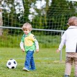 Twee kleine sibling jongens die voetbal en voetbal spelen stock afbeelding