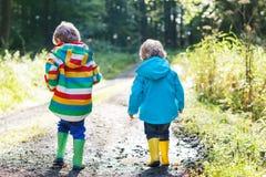 Twee kleine sibling jongens in het kleurrijke regenjassen en laarzen lopen Stock Afbeeldingen