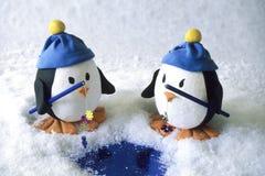 Twee kleine stuk speelgoed pinguïnen visserij Stock Fotografie