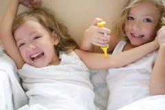 Twee kleine tweelingzusters, spel artsen met spuit Stock Afbeeldingen