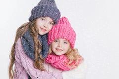 Twee kleine zusters die in de winterkleren koesteren Hoeden en sjaals Roze en grijs Familie De winter Stock Afbeelding