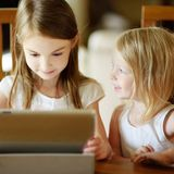 Twee kleine zusters die digitale tabletcomputer met behulp van Stock Afbeeldingen