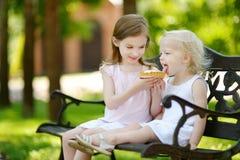 Twee kleine zusters die heerlijke scherpe room delen royalty-vrije stock afbeeldingen