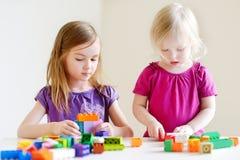 Twee kleine zusters die met kleurrijke blokken plaing Royalty-vrije Stock Fotografie