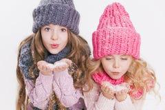 Twee kleine zusters die op de sneeuwvlokken in de winterkleren blazen Hoeden en sjaals Roze en grijs Familie De winter Stock Foto's